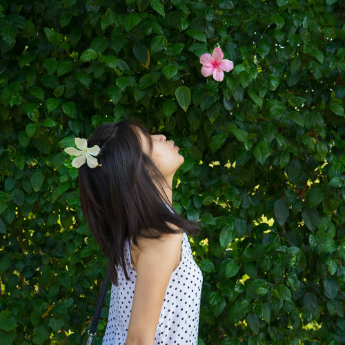 Side View Of Teenage Girl Trying To Kiss Pink Flower At Park