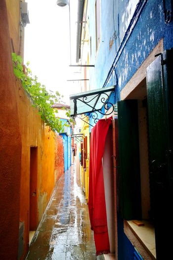 The colourful streets of Burano Italy Blue Red Wet Window Coulourful Burano EyeEmNewHere EyeEm Best Shots HuaweiP9 Huaweiphotography Streetphotography City Clothesline Wet Architecture Building Exterior Built Structure Sky Alley Narrow Drying Walkway Wall Lamp Long Pathway Residential Structure Cloth Lane