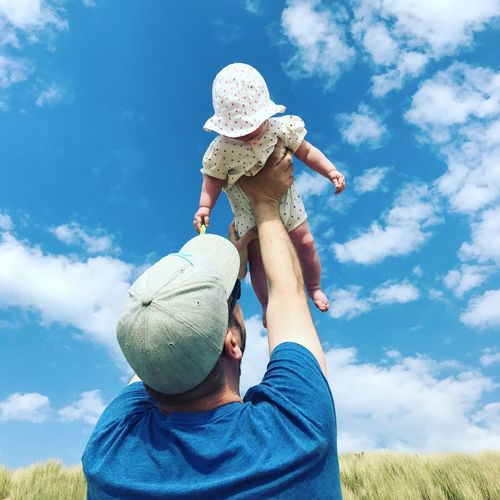 Low angle view of man holding daughter against sky