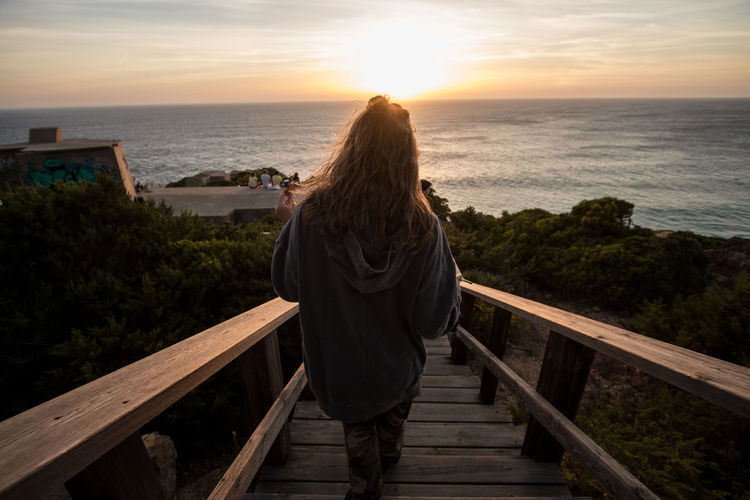 Rear View Of Woman Looking At Sea While Standing On Steps Against Sky During Sunset