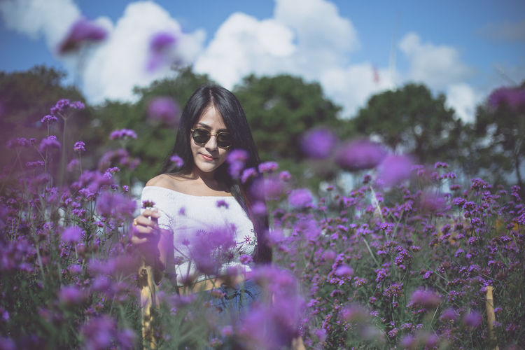 Woman Amidst Purple Flowers On Field