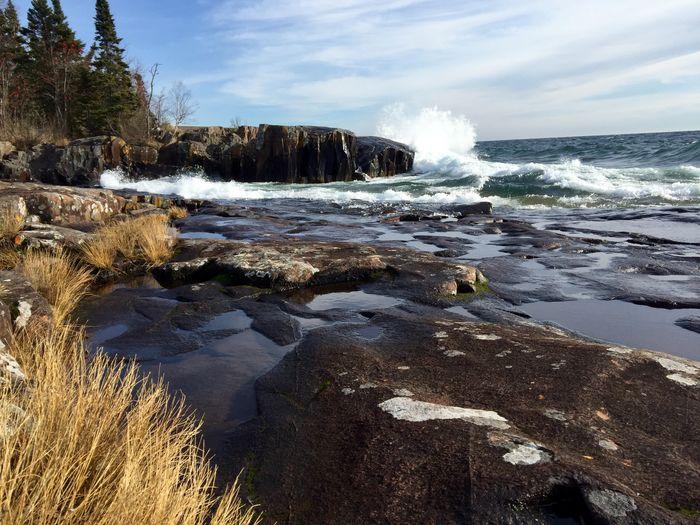 Sea Waves Splashing On Rock Formation Against Sky