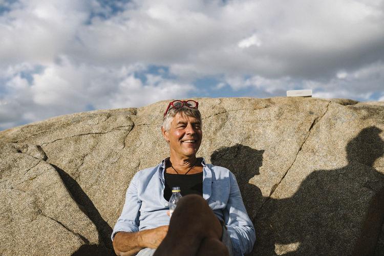 Full length of smiling man standing on rock against sky