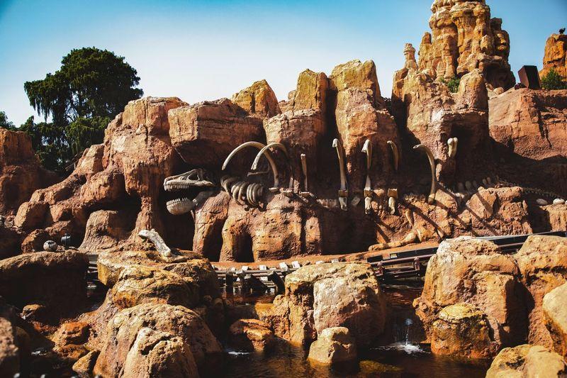 Dinosaur bone on rock formations against clear sky