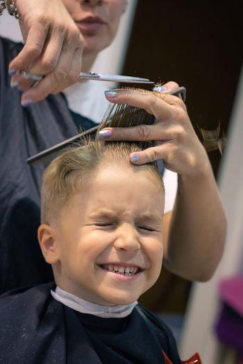 Woman cutting hair of boy at salon