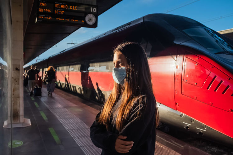 Teenage girl with face mask  checking departure timetable board at railroad station in venice, italy
