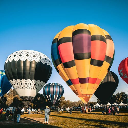 Multi colored hot air balloon flying against clear sky