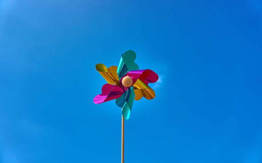 Low angle view of pinwheel against blue sky