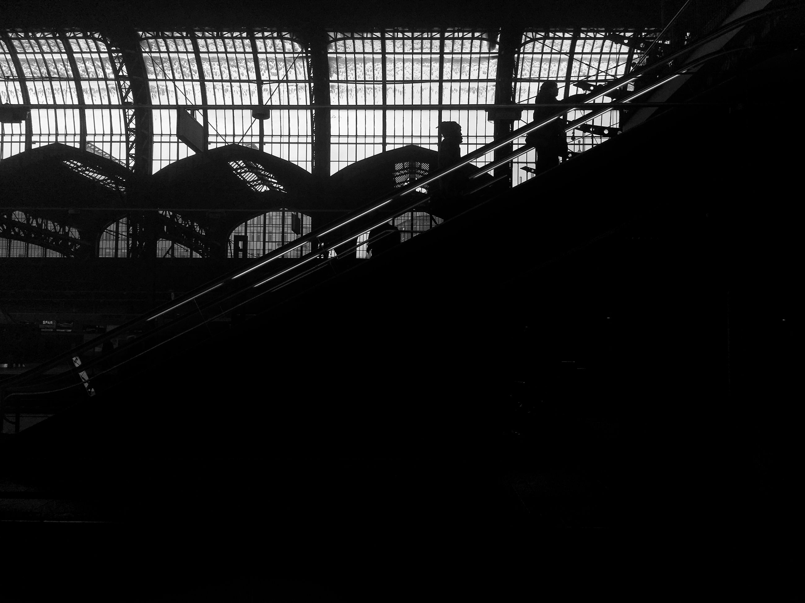 architecture, built structure, indoors, metal, low angle view, railing, silhouette, building exterior, window, no people, building, day, sunlight, metallic, illuminated, railroad track, ceiling, interior, rail transportation, dark