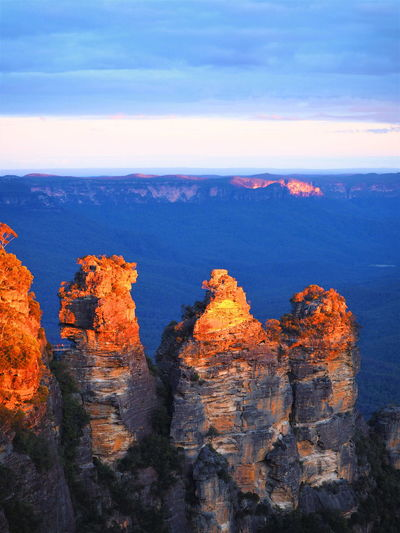 Three Sisters in Blue Mountains of New South Wales, Australia Sky Rock Scenics - Nature Beauty In Nature Nature Mountain No People Non-urban Scene Environment Cloud - Sky Travel Landscape Travel Destinations Three Sisters Blue Mountains Katoomba, NSW, Australia, Sydney Australia Trip Tourist Tourist Attraction  Tourist Destination Blue Sky Blue Mountains Backgrounds Golden Twilight Twilight Sky Twilightscapes Bush Forest Visit Visitor Orange Color Gold Color Shiny Group Of Rocks Outlook Scenics Scnery Sunst