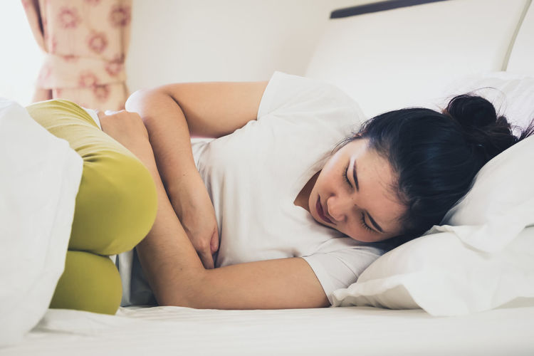 Woman with stomachache sleeping on bed