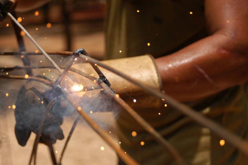 Mid section of man welding metal in workshop