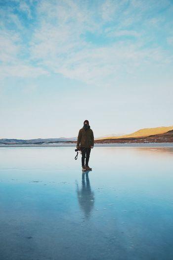 Full length of man standing on salt lake against sky