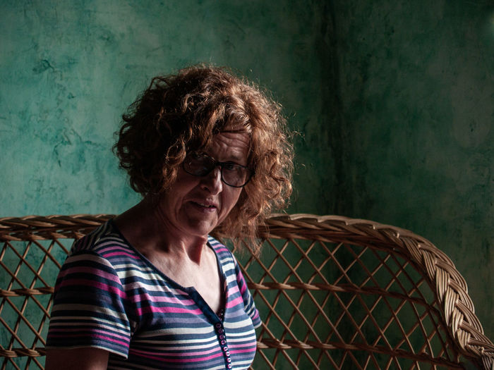 Portrait Of Woman Sitting On Seat At Home