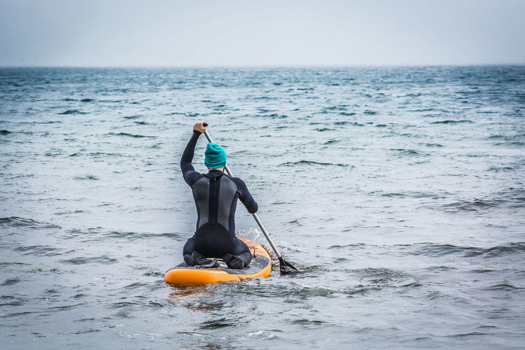 Rear View Of Man Paddleboarding In Sea