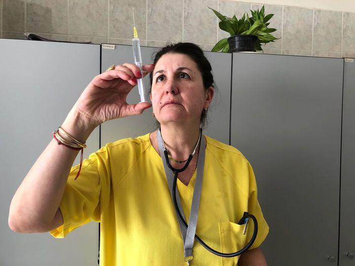 Nurse looking at syringe in hospital