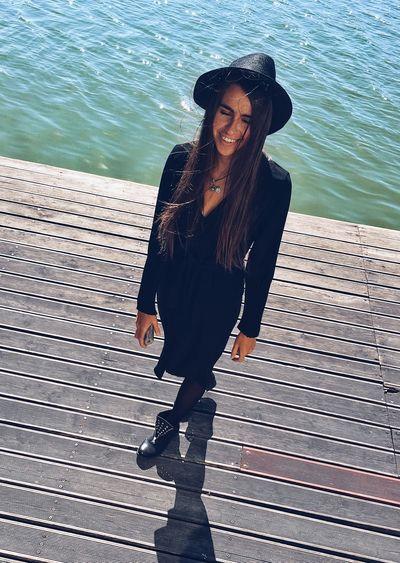Full length of woman standing on pier over lake