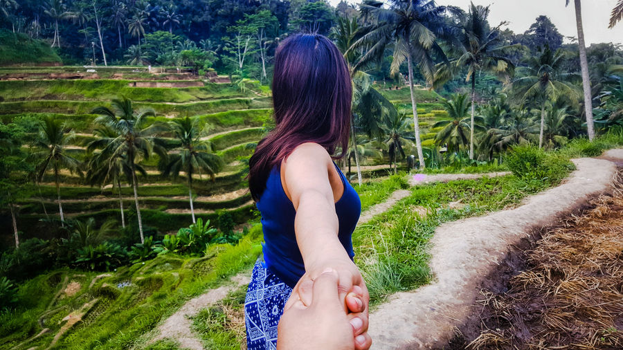 Cropped image of man holding woman hand against trees