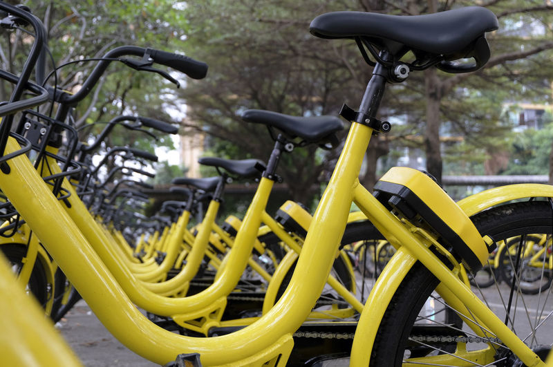 Rows of bright yellow public rental bikes on a street. Bicycle Bicycle Rack Close-up Day Land Vehicle Metal Mode Of Transport No People Outdoors Stationary Transportation Wheel Yellow
