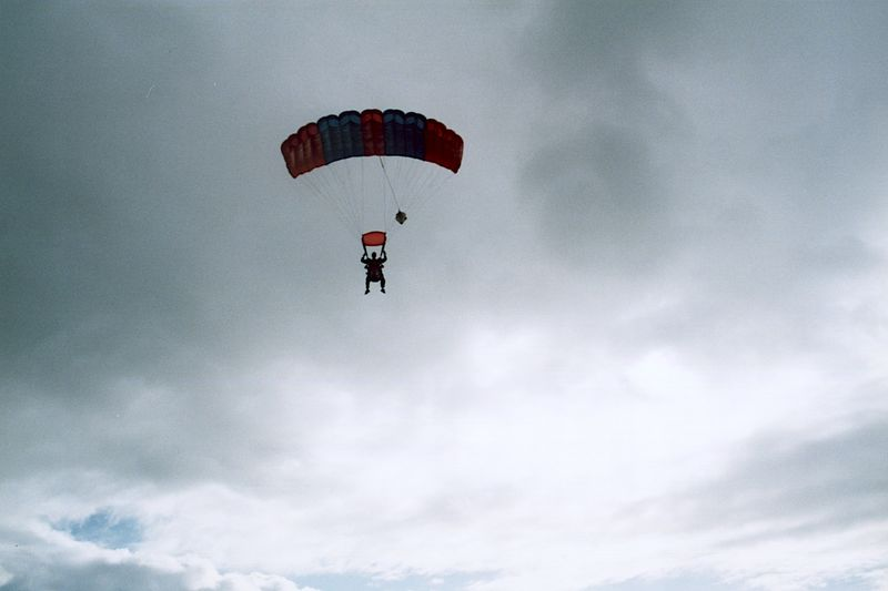 Low angle view of paragliding against cloudy sky