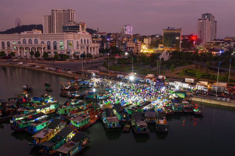 Aerial view of illuminated boats at harbor by buildings in city at night