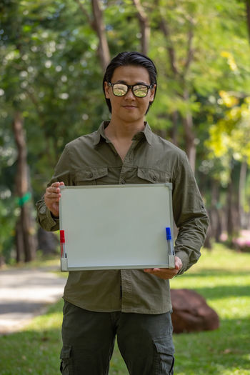 Portrait of young man wearing sunglasses standing against trees