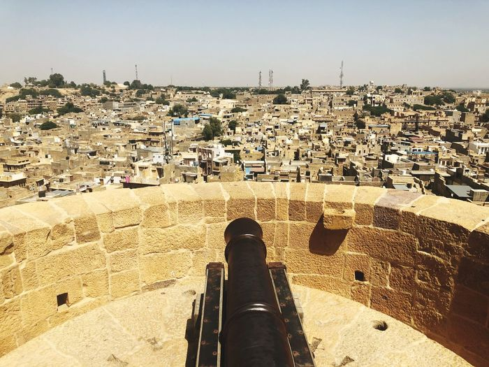 High angle view of cannon on terrace against buildings and sky