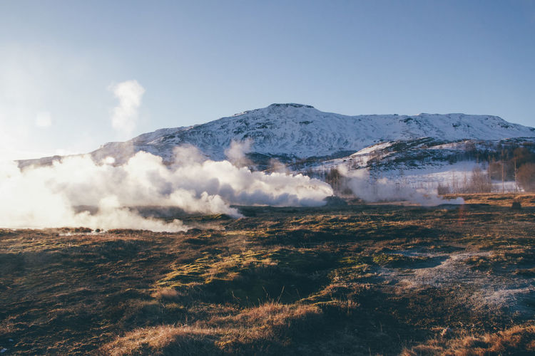 Scenic view of steam and mountain against sky