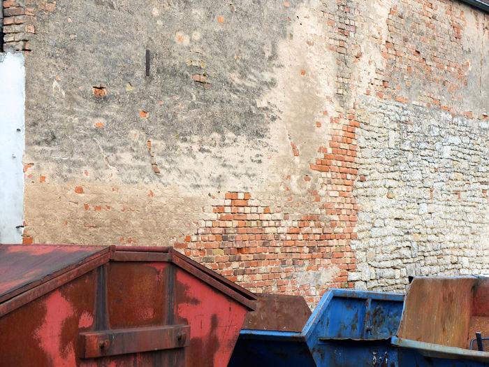 Garbage Bins Against Brick Wall
