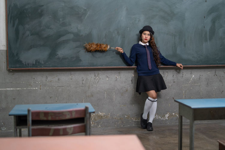 Portrait of young woman holding cleaning product while standing by blackboard in classroom