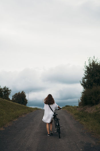 Leaving Leaving Bike Cycling White Dress Girl Woman Her Power Freedom Full Length Women Rural Scene Road Sky Cloud - Sky Empty Road Countryside Mountain Road Storm Cloud Atmospheric Mood Tranquil Scene Be Brave