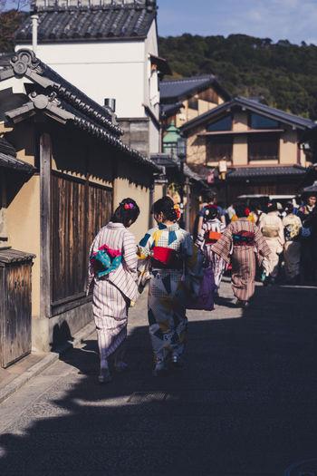 Rear view of people walking on street against buildings in city