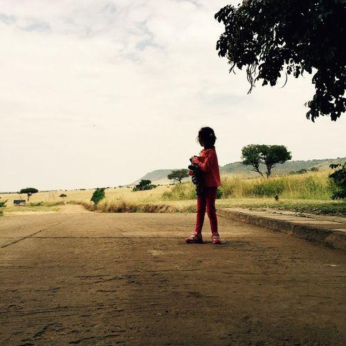 Full length of girl standing on road against sky