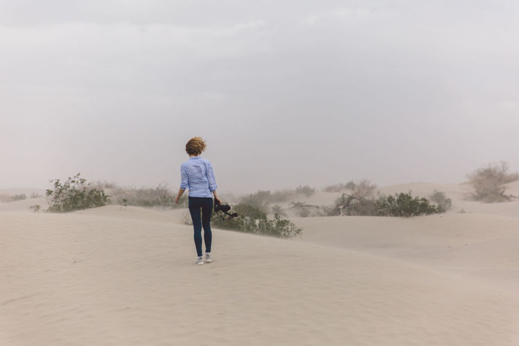 Arid Climate Arid Landscape Beauty In Nature Childhood Curly Hair Day Death Valley Death Valley National Park Desert Dunes Full Length Girl Landscape Nature One Person Outdoors People Real People Rear View Sand Storm Sky Standing Storm Tree Walking