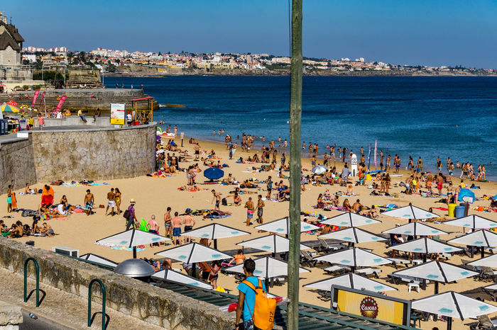 Beach at Cascais, Portugal on a sunny day. Bathers on the beach. Tourists Architecture Bathers Beach Blue Building Exterior Built Structure City Cityscape Clear Sky Crowd Day High Angle View Holidaymakers Horizon Over Water Large Group Of People Leisure Activity Lifestyles Men Nature Outdoors People Real People Sea Sky Summer Sunlight Water Women