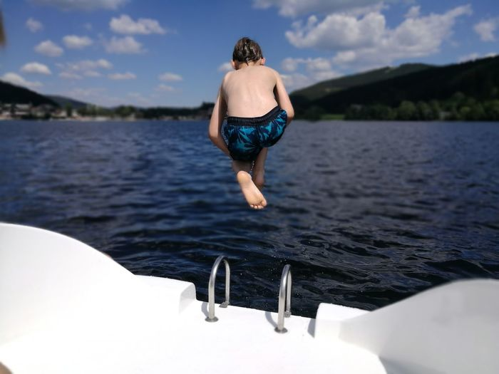 Rear View Of Shirtless Boy Jumping In Sea