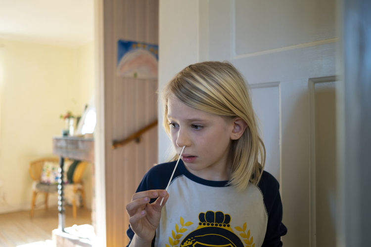 Portrait of girl holding mobile phone at home