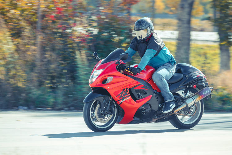 Biker Casual Clothing Crash Helmet Day Focus On Foreground Full Length Helmet Land Vehicle Leisure Activity Lifestyles Mode Of Transportation Motion Motorcycle Nature One Person Outdoors Real People Ride Riding Road Sitting Transportation Tree