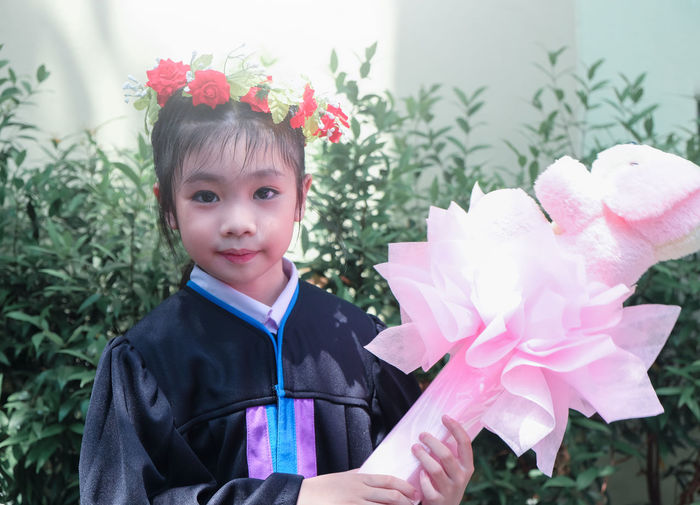 Portrait of smiling boy holding flowers