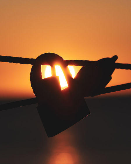 Close-up of silhouette hand against orange sky during sunset