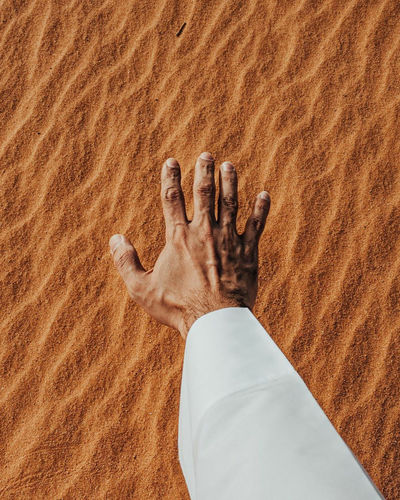 Cropped hand of man gesturing against sand in desert