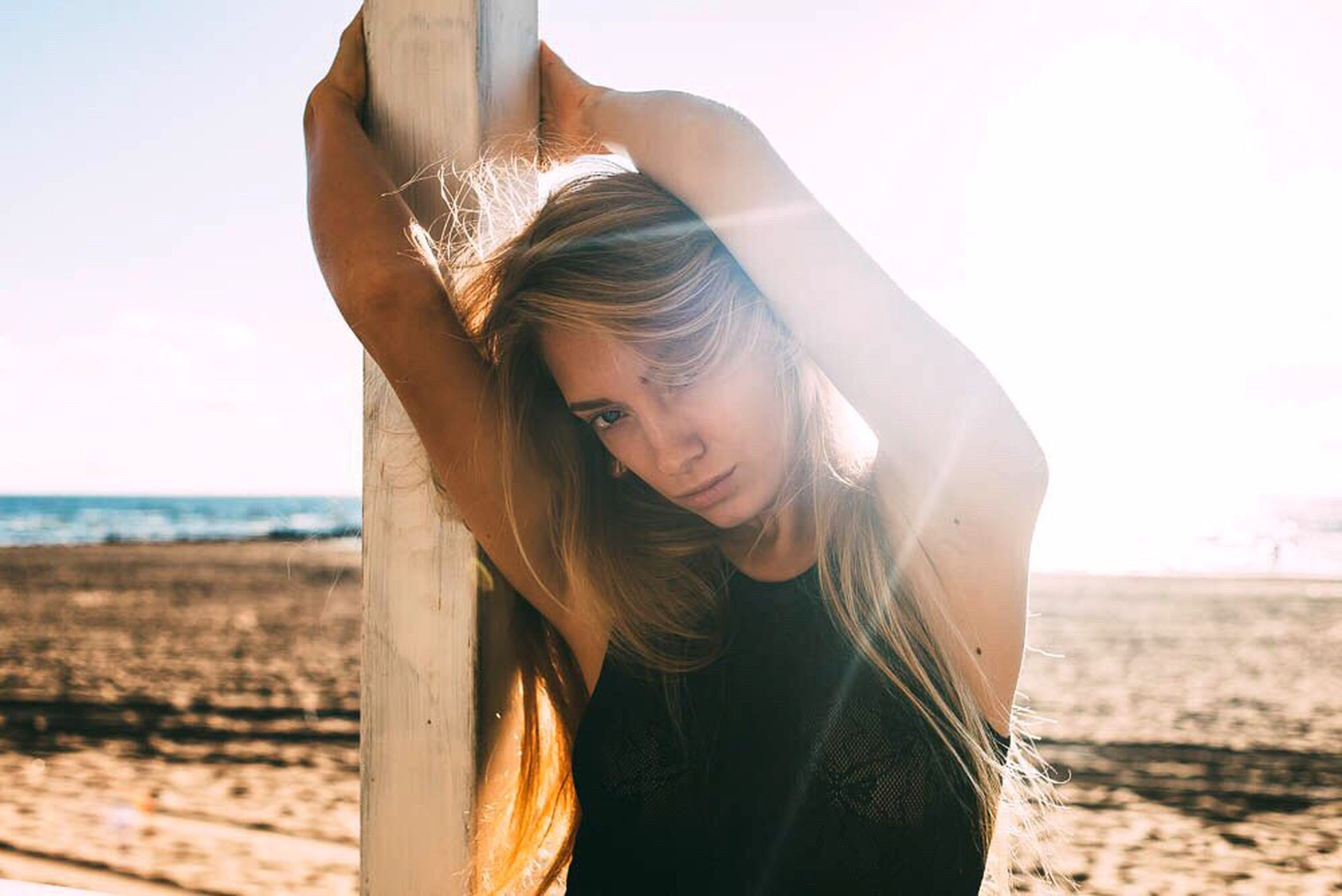 beach, sea, horizon over water, clear sky, water, shore, young adult, sand, lifestyles, leisure activity, focus on foreground, sky, tranquility, nature, person, long hair, standing, young women