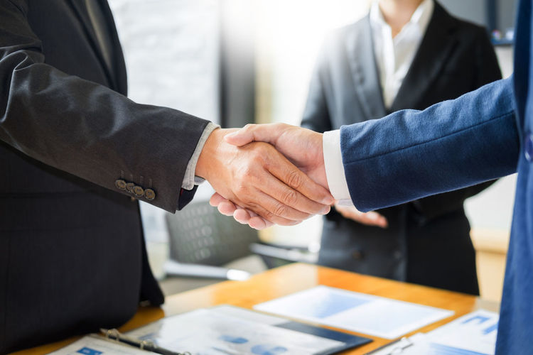 Business Business Person Well-dressed Corporate Business Office Men Handshake Meeting Cooperation Partnership - Teamwork Agreement Businessman Teamwork Adult Midsection Communication Males  Table Suit Formalwear Hand Greeting Coworker Formal Businesswear