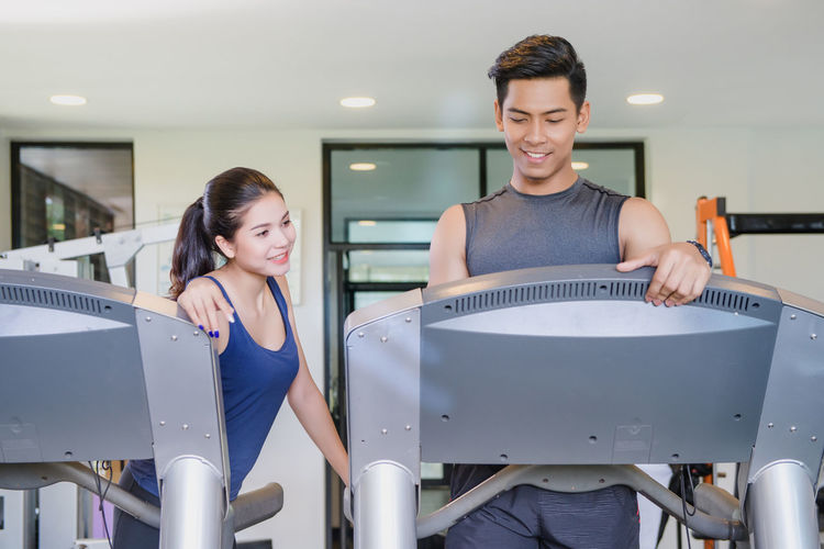Man and women working out in gym together Sitting Young Adult Adult Indoors  Two People Smiling Real People Young Women People Portrait Lifestyles Front View Casual Clothing Men Happiness Togetherness Fitness Gym Fitness Training Excercising