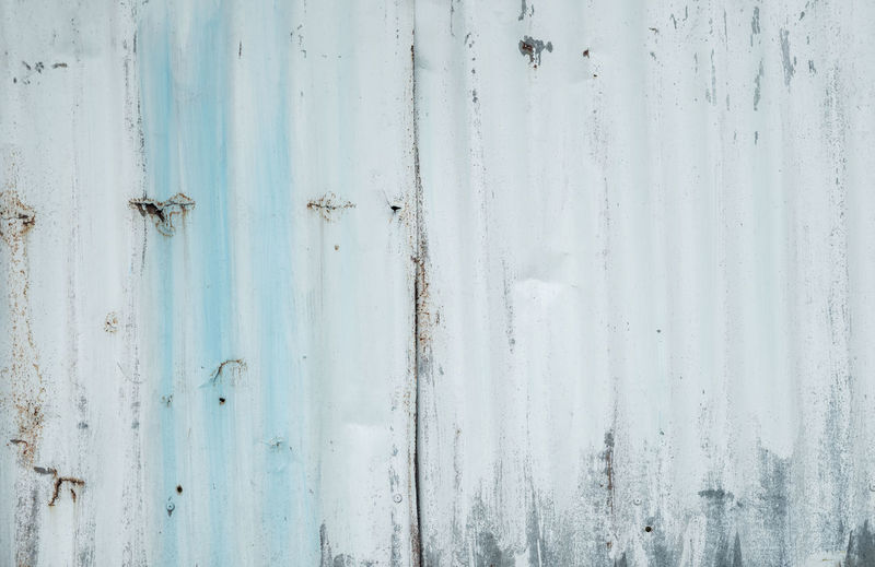 Galvanized sheet painted with white color. empty white wall texture background. peeling paint.