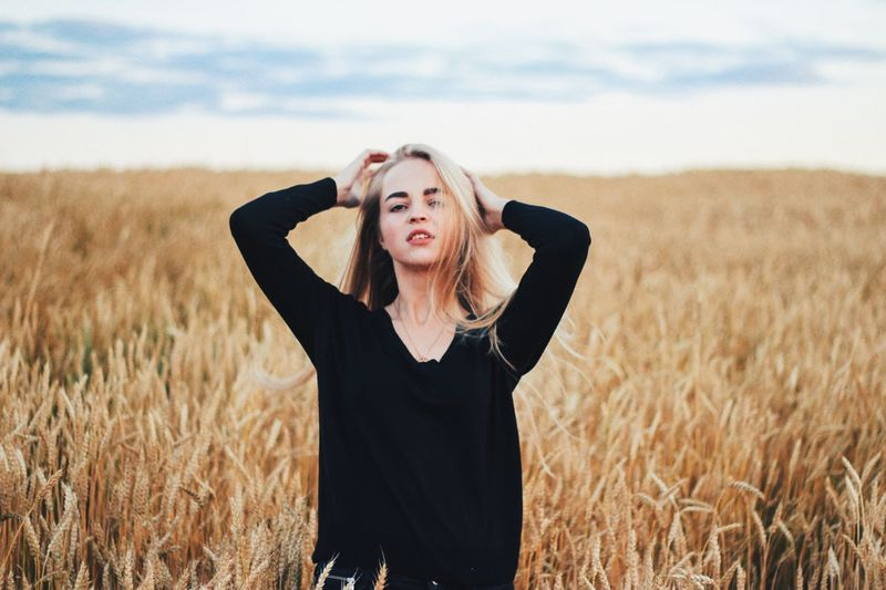 Portrait of beautiful woman standing at wheat farm