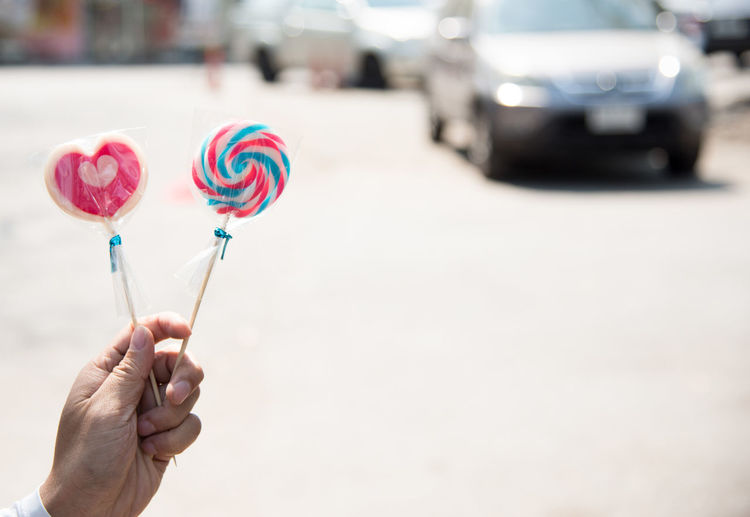 Cropped hand having lollipops on road