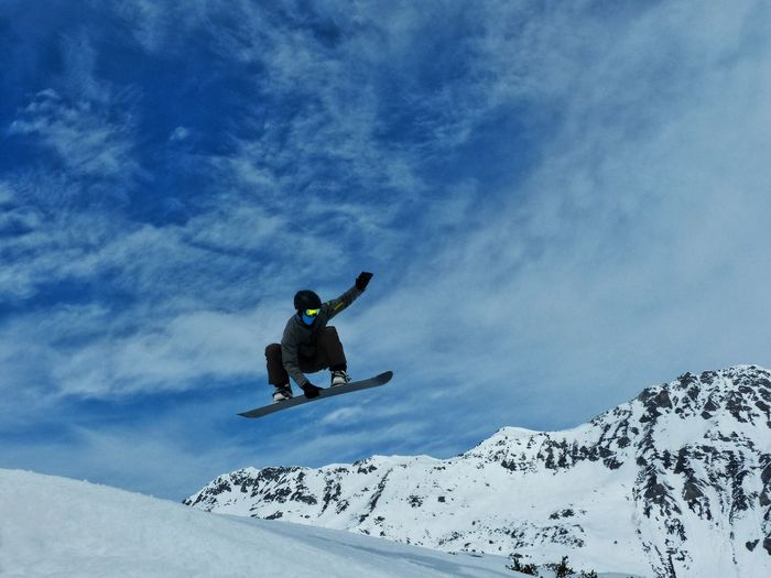 Low angle view of man snow boarding