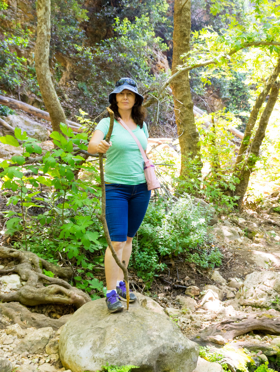 Full Length Portrait Of Woman With Stick Standing On Rock In Forest