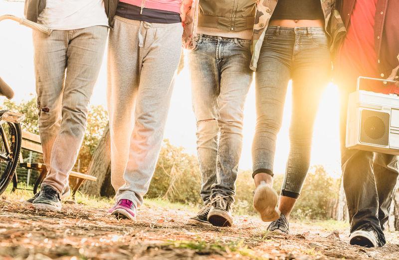 Low section of friends walking on field